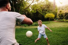 Father and son playing football in backyard garden Stock Photography