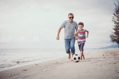 Father and son playing football on the beach at the day time. stock photography