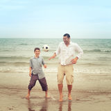 Father and son playing with a football on the beach. Father playing with a football on the beach while his son watches Royalty Free Stock Photos