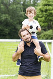 Father with son playing football on football pitch. A father with son playing football on football pitch Royalty Free Stock Photos