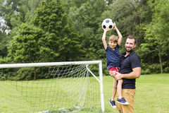 Father with son playing football on football pitch. A father with son playing football on football pitch Royalty Free Stock Image