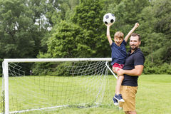 Father with son playing football on football pitch. A father with son playing football on football pitch Stock Images