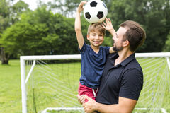 Father with son playing football on football pitch. A father with son playing football on football pitch Stock Photography