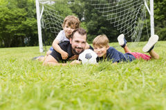 Father with son playing football on football pitch. A father with son playing football on football pitch Royalty Free Stock Photo