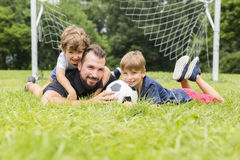 Father with son playing football on football pitch. A father with son playing football on football pitch Royalty Free Stock Images
