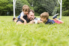 Father with son playing football on football pitch stock photos