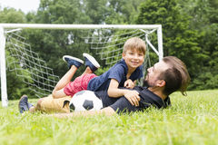 Father with son playing football on football pitch. A father with son playing football on football pitch Stock Photos