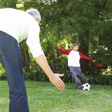 Father and son playing football in a garden Stock Image