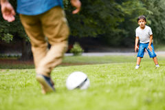 Father and son playing football in the park. Father with his son playing football on the green grass in the park. Boy is very excited Stock Images