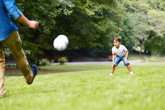 Father and son playing football in the park. Father with his son playing football on the green grass in the park. Boy is very excited Stock Photo