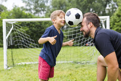Father with son playing football on football pitch. A father with son playing football on football pitch Royalty Free Stock Photography