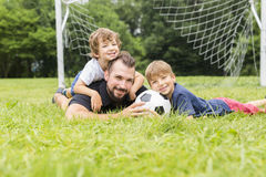 Father with son playing football on football pitch. A father with son playing football on football pitch Stock Image