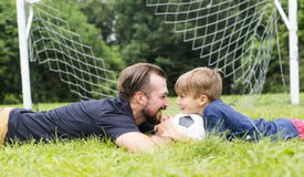 Father with son playing football on football pitch. A father with son playing football on football pitch Stock Photo