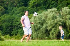Father and son playing football. Father with a small son play football on a green lawn Stock Photo