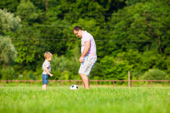 Father and son playing football. Father with a small son play football on a green lawn Stock Photography