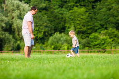 Father and son playing football. Father with a small son play football on a green lawn stock images