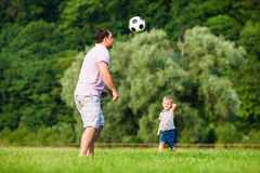 Father and son playing football. Father with a small son play football on a green lawn Stock Photos