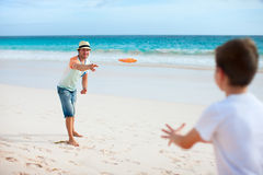Father and son playing frisbee. At beach Stock Photography