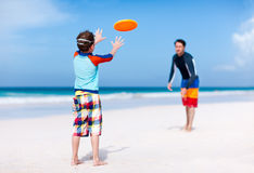 Father and son playing frisbee. At beach Royalty Free Stock Photos