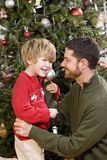 Father and son playing in front of Christmas tree Stock Photography