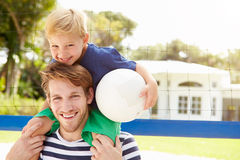 Father And Son Playing Game Of Volleyball In Garden Stock Photo