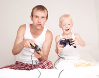 Father and son playing games. Happy family;  father and his little son playing computer games on the bed at home Royalty Free Stock Photography