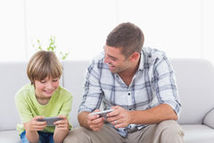 Father and son playing games on cell phone Stock Photos