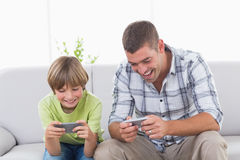 Father and son playing games on mobile phone Stock Image