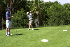 Father and son playing golf. Father and son on the tee box. Son practicing, while father is looking at him Stock Image