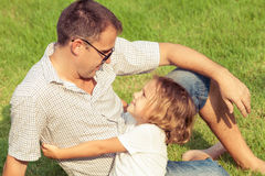 Father and son playing on the grass at the day time. Stock Image