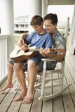Father and Son Playing Guitar. Son sits on his father's lap while playing guitar. Vertical shot Royalty Free Stock Photography