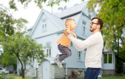 Father with son playing and having fun. Family, childhood, fatherhood, leisure and people concept - happy father and little son playing and having fun over house Stock Photography