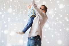 Father with son playing and having fun at home. Family, childhood, fatherhood, leisure and people concept - happy father and little son playing and having fun at Stock Photography