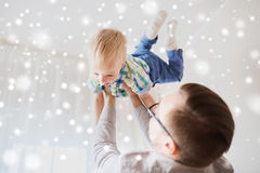 Father with son playing and having fun at home. Family, childhood, fatherhood, leisure and people concept - happy father and little son playing and having fun at Stock Photos