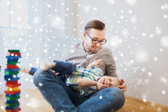 Father with son playing and having fun at home. Family, childhood, fatherhood, leisure and people concept - happy father and little son playing and having fun at Royalty Free Stock Photo