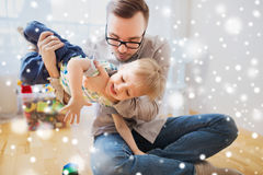 Father and son playing and having fun at home. Family, childhood, fatherhood, leisure and people concept - happy father and little son playing and having fun at Royalty Free Stock Photo
