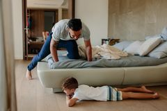 Father and son playing hide and seek in bedroom. Little boy hiding by the bed with father searching him. Family playing games inside their home Stock Photo