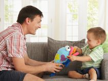 Father and son playing at home stock photography