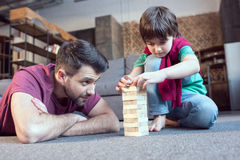 Father and son playing jenga game at home. Focused father and son playing jenga game at home Stock Photography
