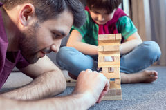 Father and son playing jenga game at home. Side view of father and son playing jenga game at home Stock Image