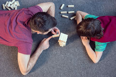 Father and son playing jenga game at home. Top view of father and son playing jenga game at home Royalty Free Stock Photography