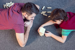Father and son playing jenga game. Top view of father and son playing jenga game Stock Photos