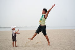 Father and Son Playing Jump On Beach Royalty Free Stock Photography