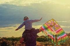 Father and son playing with a kite , in the evening in the field. Father and son playing with a kite , in the evening in field at sunset Stock Photo