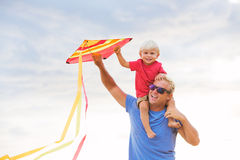 Father and son playing with kite Stock Images