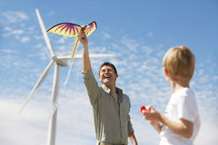 Father And Son Playing With Kite At Wind Farm. Father and son playing with dragon kite near turbine at wind farm Stock Images