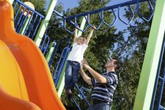 Father and son playing on monkey bars. At the park Royalty Free Stock Images