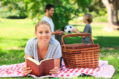 Father and son playing while the mother is reading. Father and son playing football while the mother is reading a book Royalty Free Stock Photos