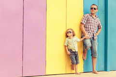 Father and son playing near the house at the day time. They standing near are the colorful wall. Concept of friendly family Royalty Free Stock Photography