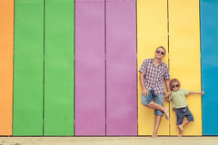 Father and son playing near the house at the day time. They standing near are the colorful wall. Concept of friendly family Royalty Free Stock Photo